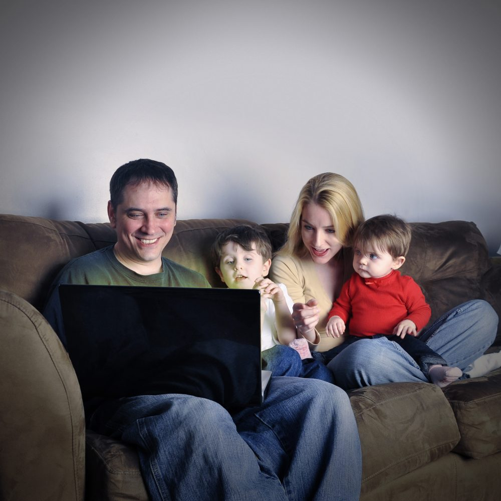 A modern family is sitting on a couch in their home watching a computer internet screen and look happy and excited. Use it for a media technology concept.